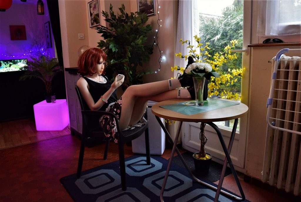 Erena a les pieds sur la table et joue avec son iPhone