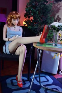 Erena regarde son iPhone avec une jambe sur la table